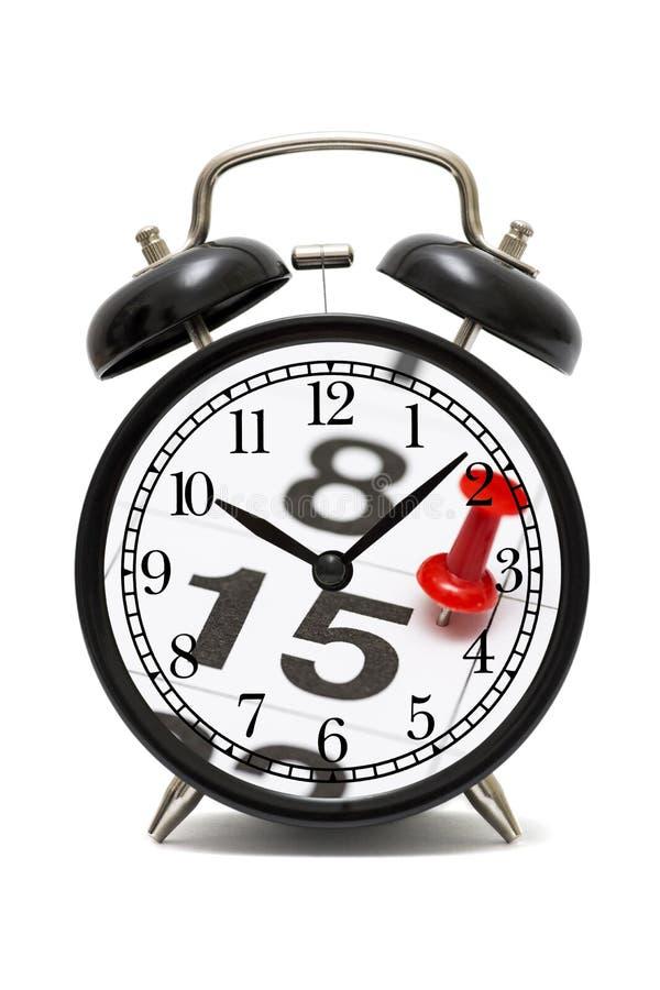 Tijd en planningsconcept Wekker en kalenderpagina met rode duwspeld op de datum nummer 15 Uiterste termijnconcept royalty-vrije stock fotografie