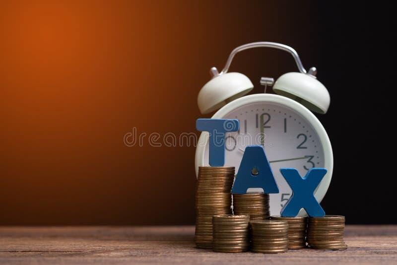 Tijd om BELASTINGSconcept te betalen BELASTINGSalfabet met stapel van muntstuk en uitstekende wekker op houten werkende lijst op  stock foto