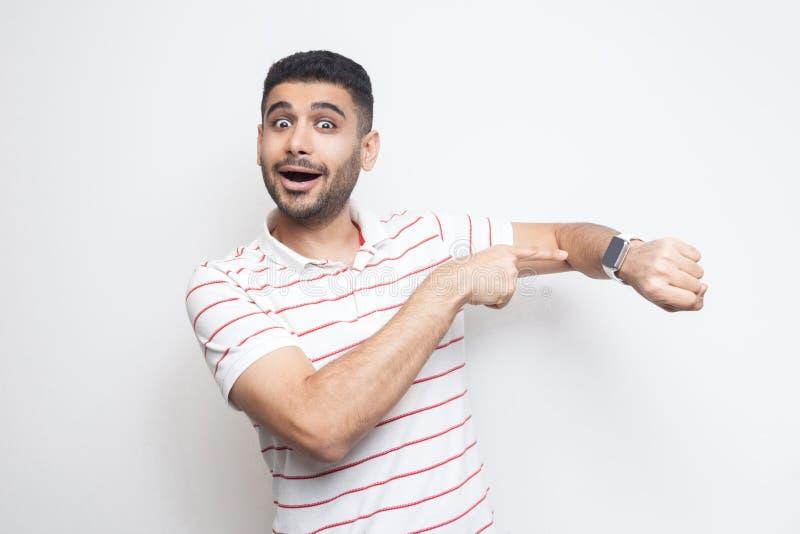 Tijd te gaan Portret van de verbaasde grappige gebaarde jonge mens in gestreepte t-shirt die, richtend op zijn slim horloge, die  royalty-vrije stock foto's