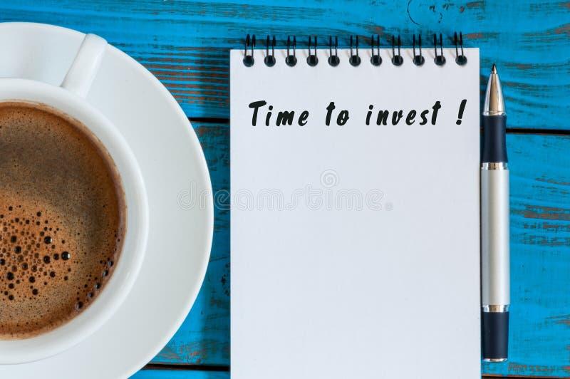 Tijd te investeren - merk in blocnote op bij blauwe houten lijst met de mok van de ochtendkoffie Besparingen, Geld bedrijfsconcep stock fotografie