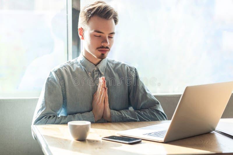 Tijd te ontspannen! Het portret van kalme knappe succesvolle gebaarde jonge freelancer in blauw overhemd zit in koffie en heeft e royalty-vrije stock afbeelding