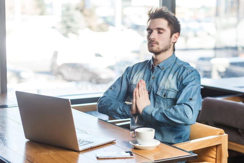 Tijd te ontspannen! Het portret van knappe succesvolle gebaarde jonge freelancer in jeansoverhemd zit in koffie en heeft een rust stock foto