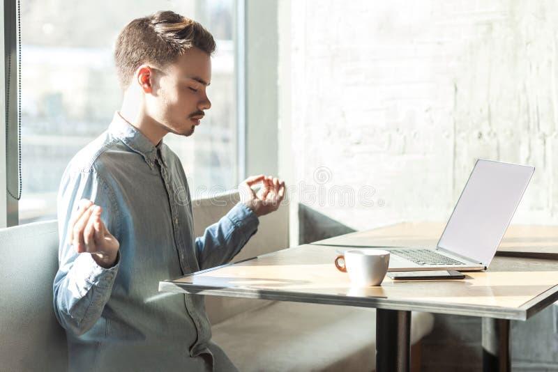 Tijd te ontspannen! het zijaanzicht van de knappe succesvolle gebaarde jonge mens in blauw overhemd zit in koffie en heeft een ru royalty-vrije stock fotografie