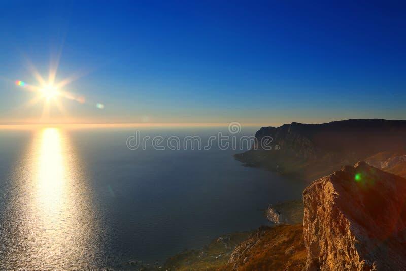 Tijd v??r zonsondergang zon, overzees en bergen stock afbeeldingen