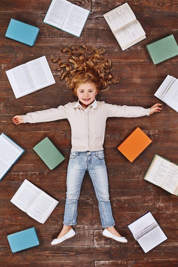 Tijd voor het dromen Meisje die dichtbij boeken, het bekijken camera en het glimlachen liggen royalty-vrije stock afbeeldingen