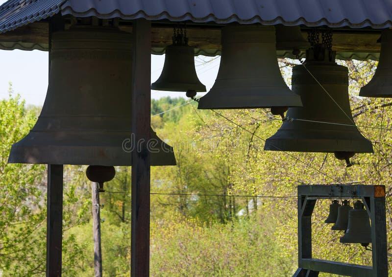 Tijdelijke klokketoren op achtergrond van groene kronen van bomen, close-up stock fotografie