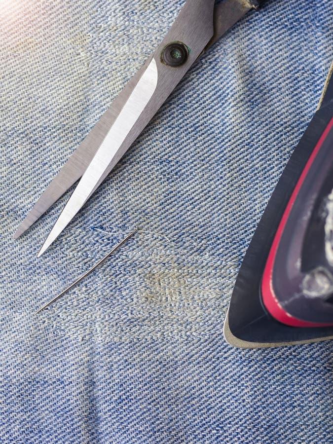Tijeras, aguja e hilo, y un hierro en el dril de algodón desigual Reparación de los vaqueros en casa imágenes de archivo libres de regalías