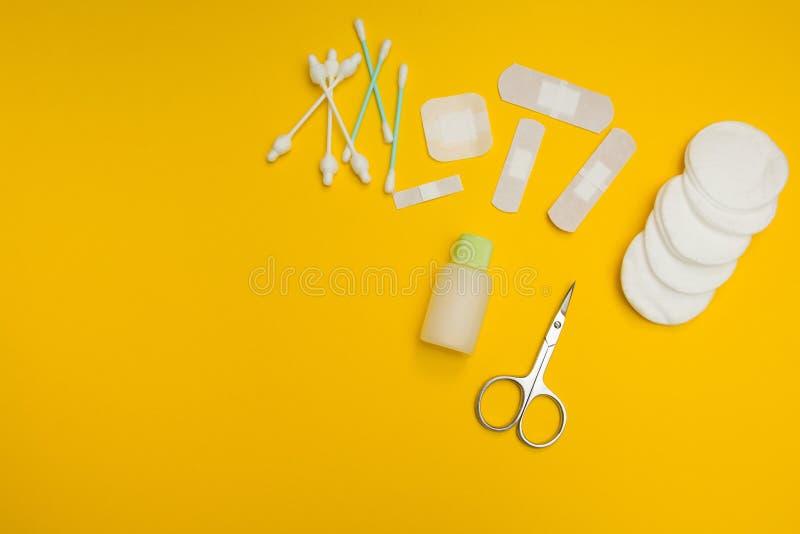 Tijeras, cinta adhesiva, esponjas de algodón y cojines en un fondo amarillo imagen de archivo