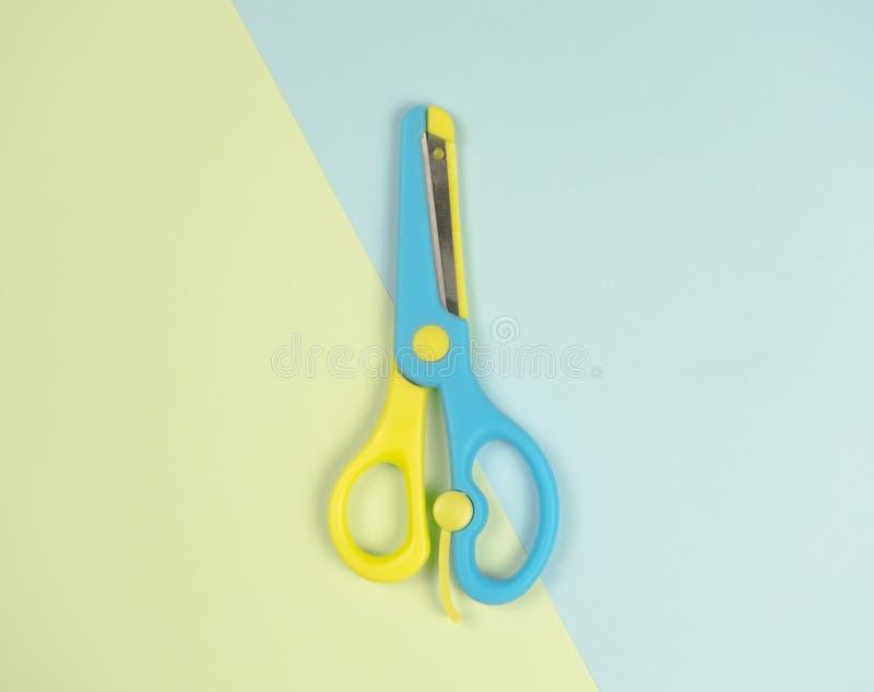 Tijeras coloridas azules y amarillas encendido en fondo azul y verde concepto colorido hermoso de la imagen lo mismo que la difer imágenes de archivo libres de regalías
