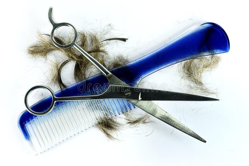 Tijeras con el pelo y el peine azul foto de archivo