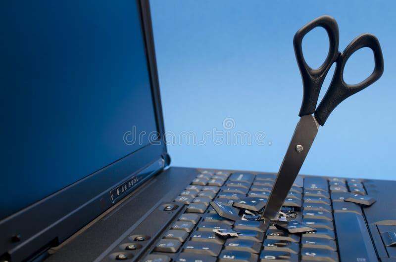 Tijeras conducidas a través de la computadora portátil imágenes de archivo libres de regalías