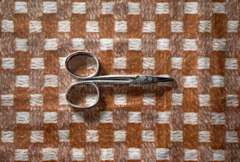 Tijeras de costura en un mantel a cuadros fotos de archivo