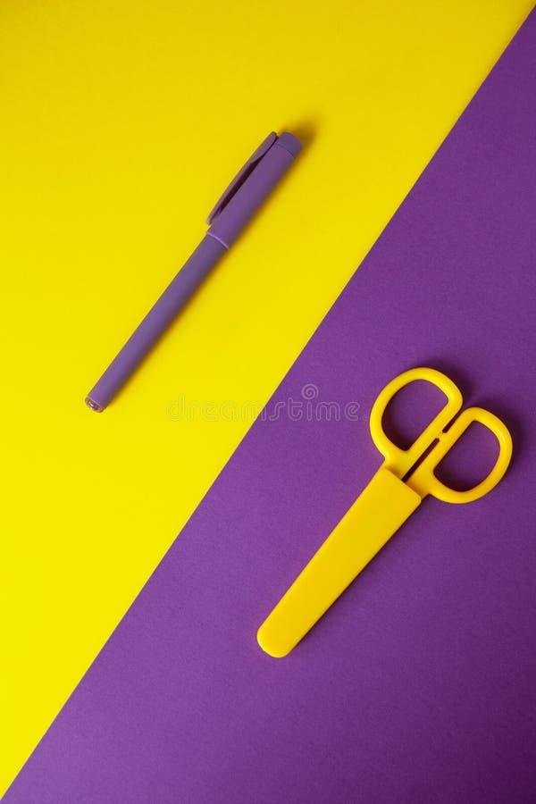 Tijeras de los efectos de escritorio del niño amarillo en el fondo púrpura, pluma púrpura en fondo amarillo imagen de archivo