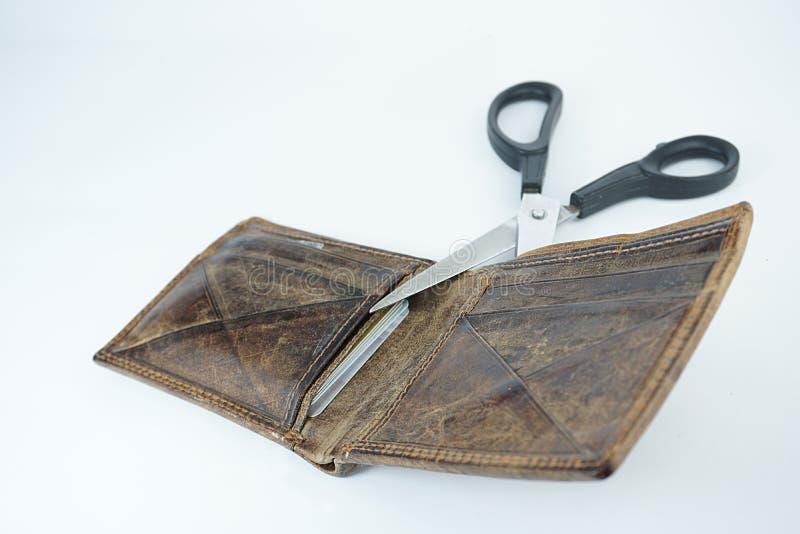 Tijeras que cortan una cartera de cuero marrón con las tarjetas de crédito imagen de archivo libre de regalías