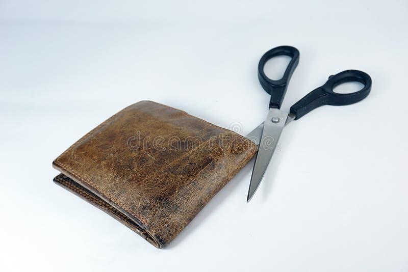 Tijeras que cortan una cartera de cuero marrón en el fondo blanco fotos de archivo