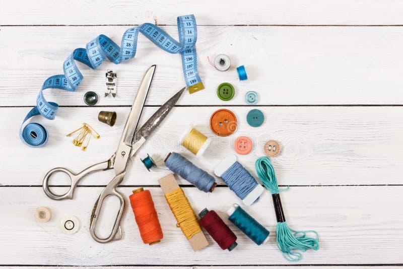 Tijeras viejas, botones, hilos, cinta métrica y suppli de costura imagenes de archivo