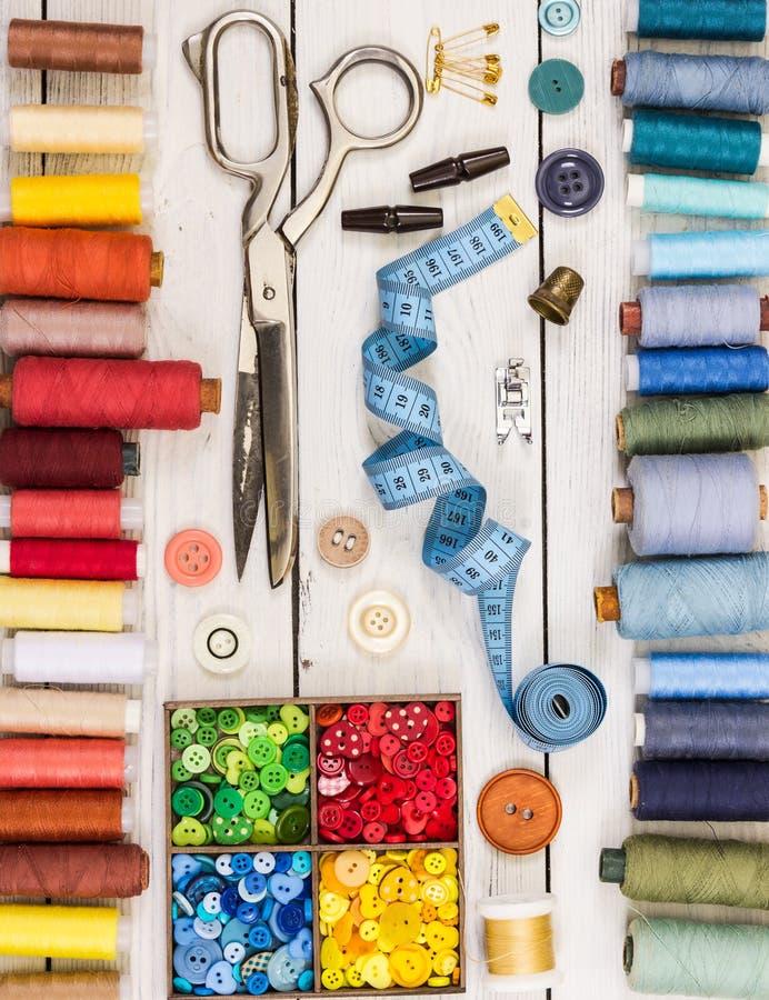 Tijeras viejas, botones, hilos, cinta métrica y suppli de costura fotos de archivo libres de regalías