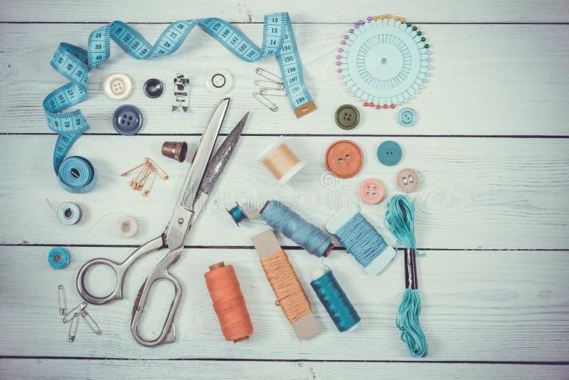 Tijeras viejas, botones, hilos, cinta métrica y suppli de costura fotografía de archivo libre de regalías