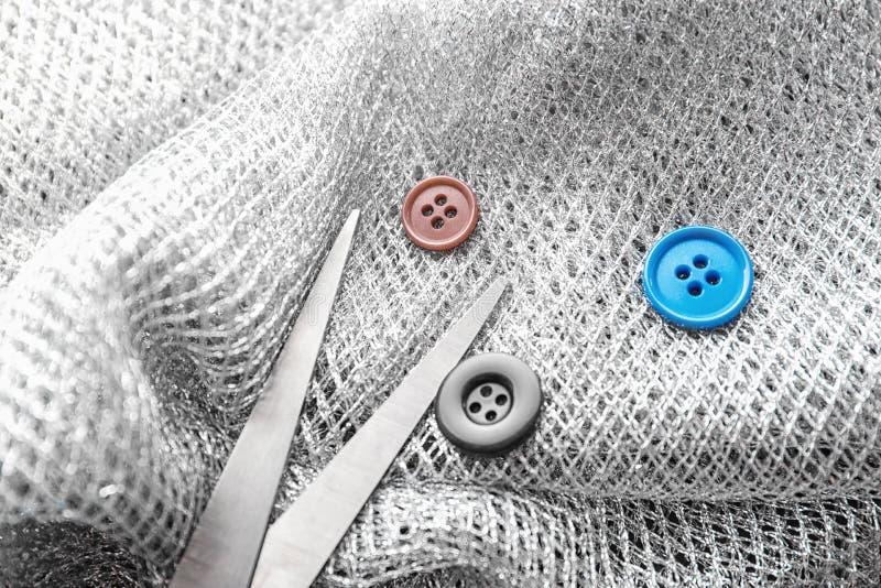 Tijeras y botones en tela imagenes de archivo