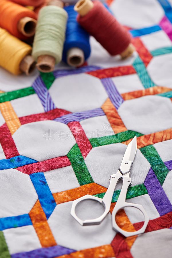 Tijeras y carretes del hilo que mienten en el top del edredón del fragmento cosido a mano de figuras geométricas fotos de archivo libres de regalías
