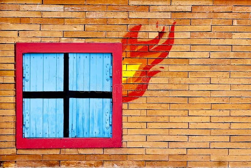 Tijolo da parede com a janela no fogo imagens de stock