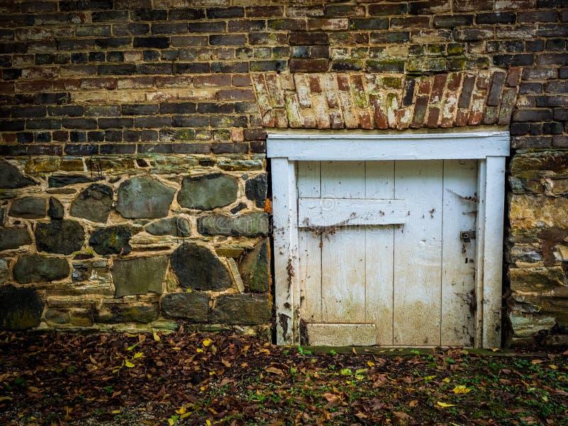 Tijolo e parede de pedra com a porta de madeira pequena foto de stock royalty free