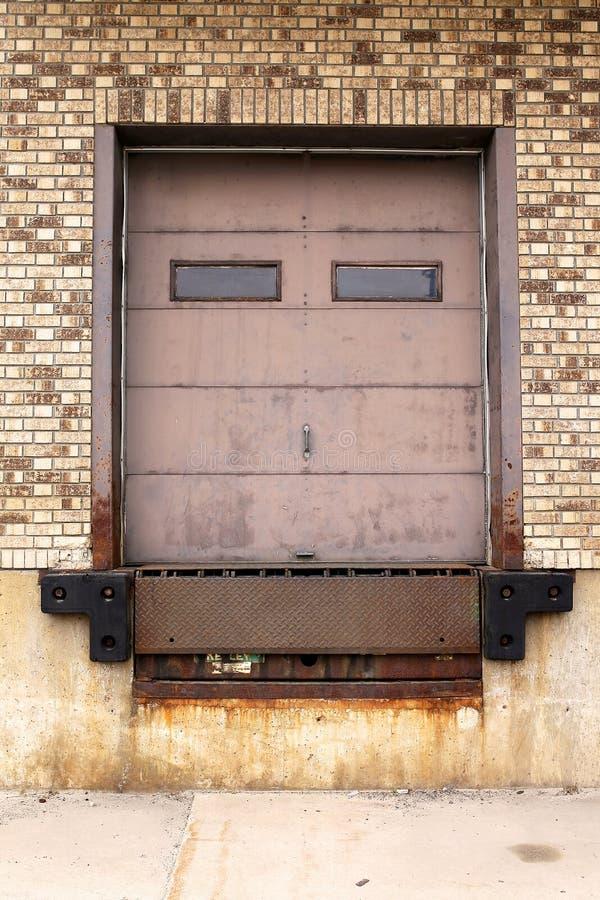 Tijolo velho e porta de Rusty Metal Truck Loading Dock a armazenar imagem de stock royalty free