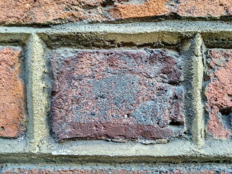 Tijolo vermelho velho com as emendas entre a alvenaria a solução do cimento é colocada uniformemente entre os tijolos fundo, fund foto de stock