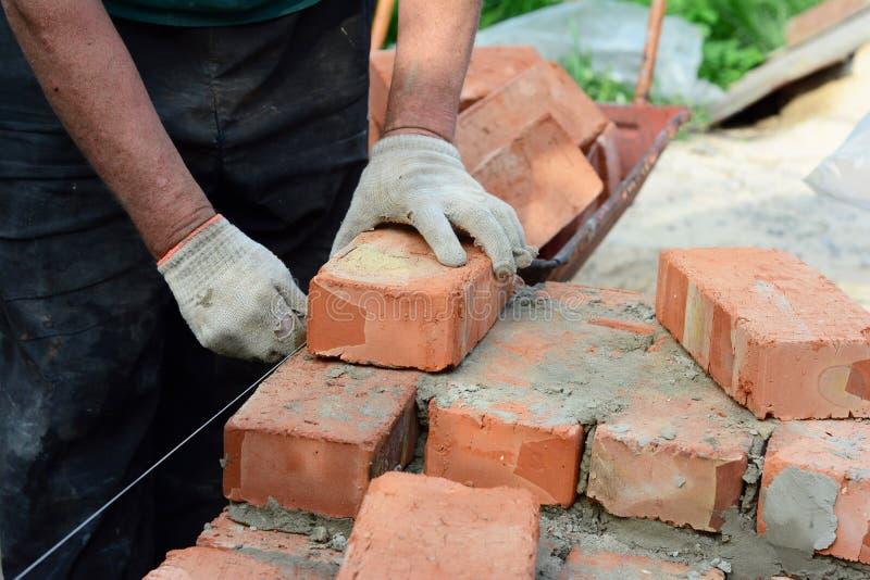 Tijolos para postura Bricklay, Masonry, Brickwork (Brickwork) sobre o novo local de construção de paredes de casas fotografia de stock