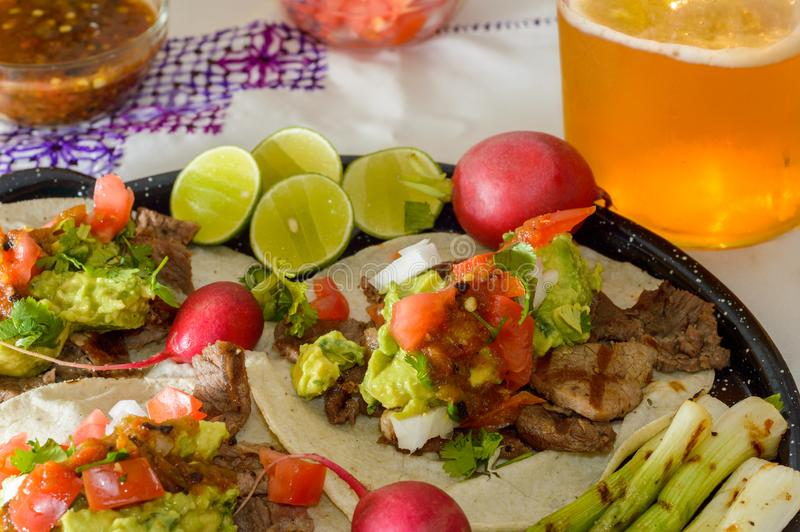 Tijuana tacos, carne asada and beer with copy space.tif. Tijuana tacos, carne asada with radishes, limes, spring onions and condiments. Served with craft beer royalty free stock photography