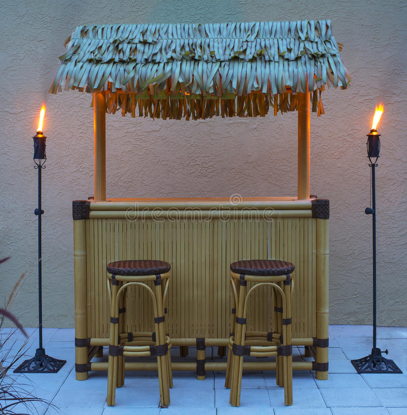 Tiki Bar at Night. Tiki bar, hut with tiki torches lit, in the backyard during the evening stock image