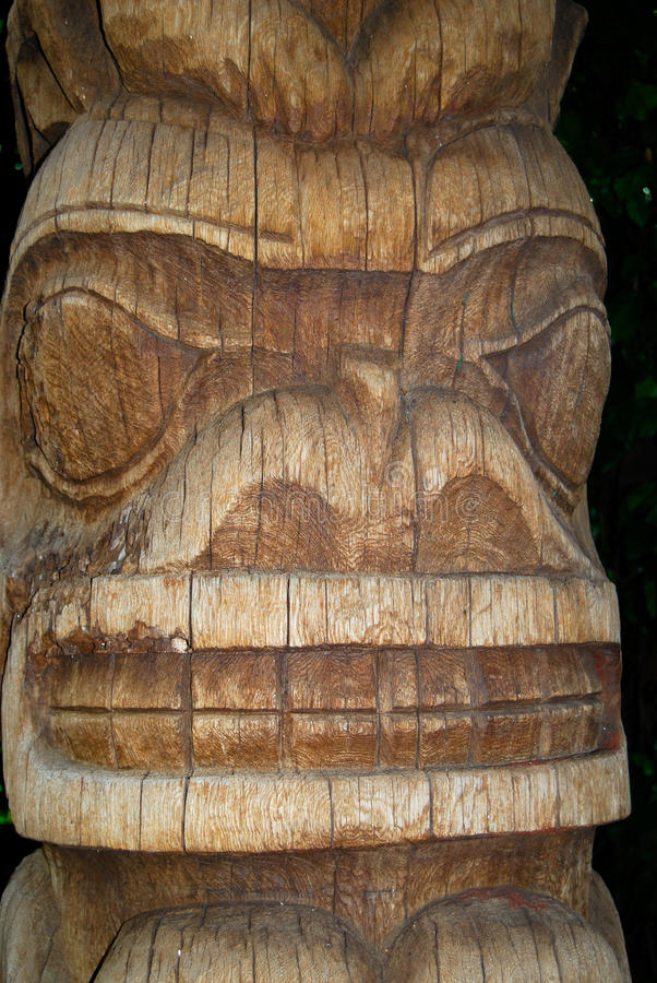 Tiki Carved Face. Close up of a wooden tiki carving with big eyes, wide nostrils and a wide grinning mouth full of teeth stock photos
