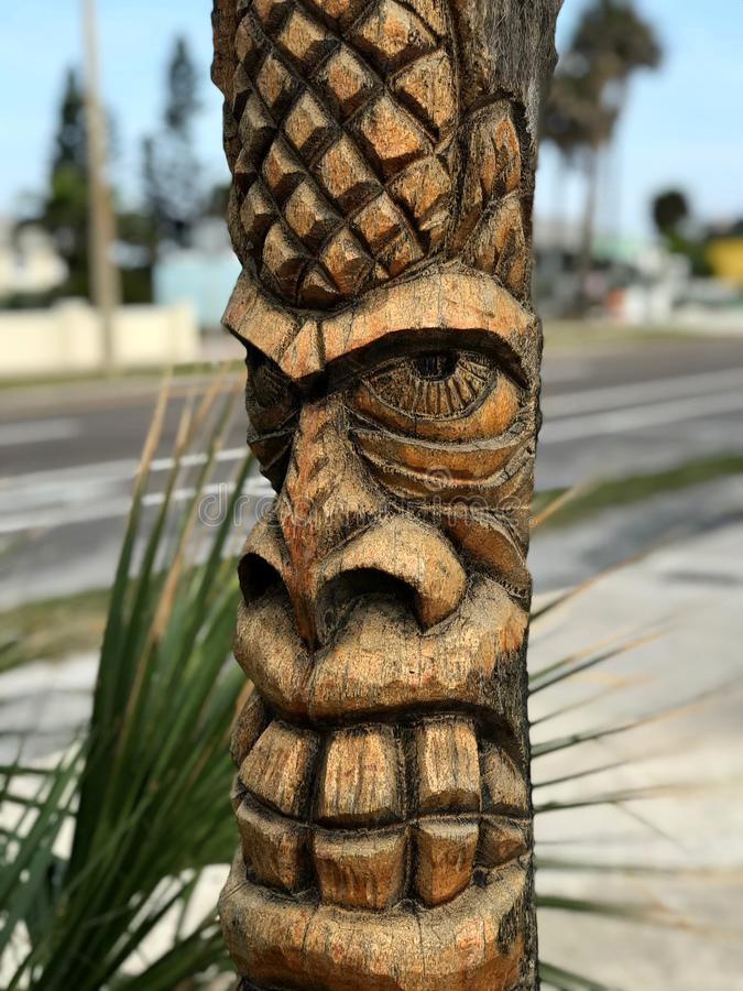 Tiki Carved Pole in Cocoa Beach . Photo image. Good Luck Humanoid wood pole in street royalty free stock photography