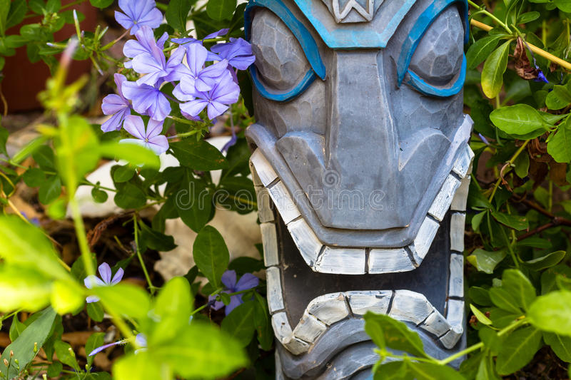 Tiki Garden. A tiki sculpture with flowers stock images