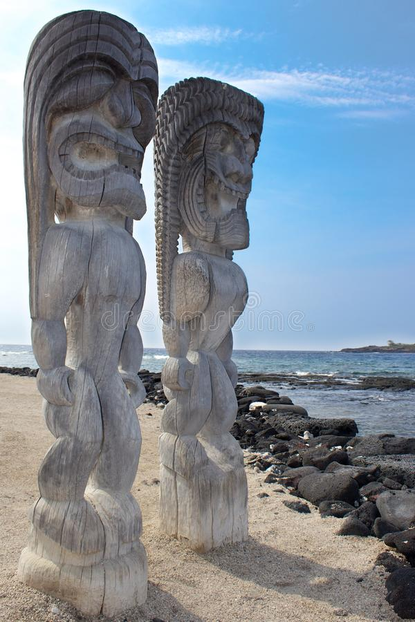 Tiki Gods. Male & Female Tiki God Statues on a beach carved out of wood in Hawaii royalty free stock images
