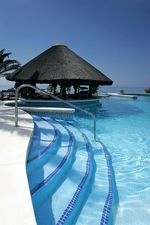 Tiki Hütte und Stab durch Swimmingpool des Luxushotels stockbilder