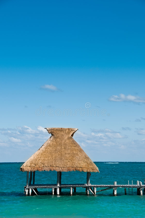 Tiki Hut. On dock with blue ocean and sky stock photo