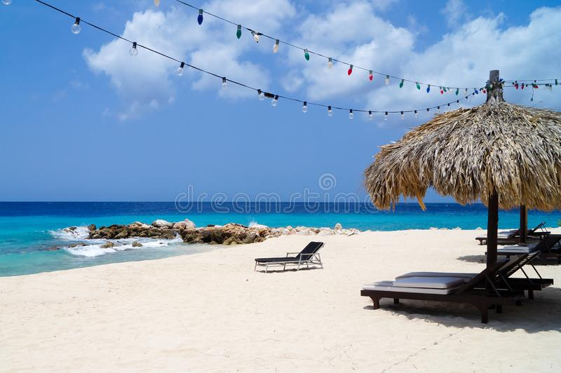 Tiki hut on the beach. With white sand, blue water and colorful lights stock photos