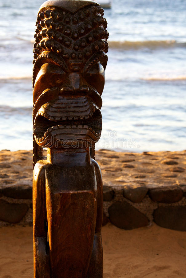 Tiki statue. A large wooden Tiki statue in the glow of the setting sun stock photo