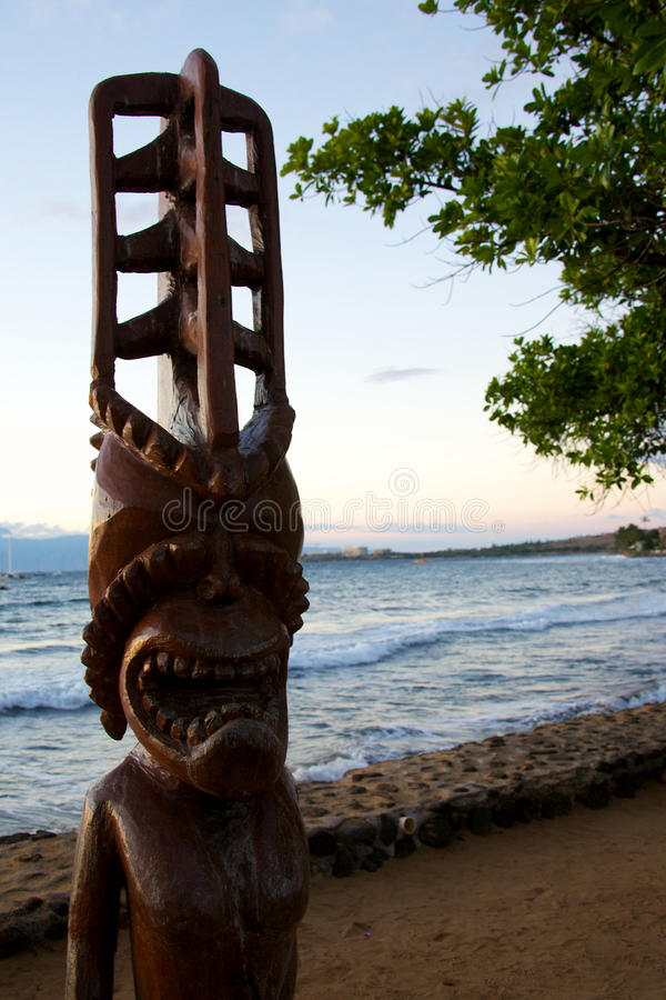 Tiki statue. A large wooden Tiki statue in the glow of the setting sun royalty free stock photo