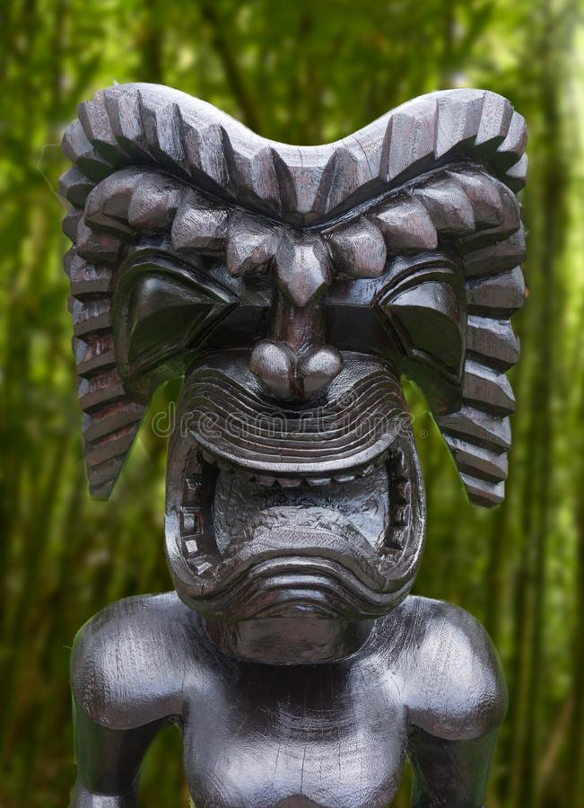 Tiki statue in topical jungle. Close up picture of ancient wooden Tiki sculpture in Hawaii. Carved deity of warrior god stock photos