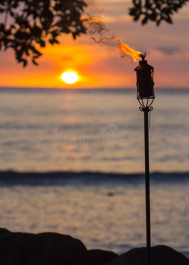 Tiki torch at sunset. A lit tiki torch with the sunset and ocean in the background royalty free stock image