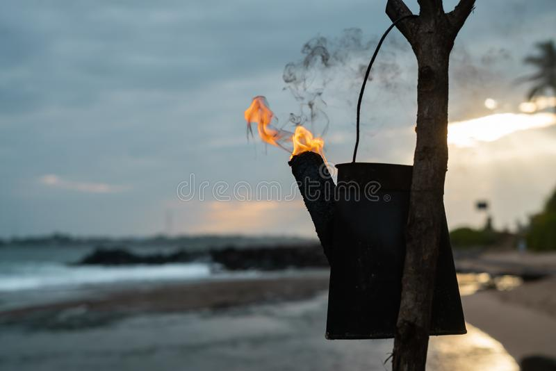 Tiki torches with a bright orange Hawaiian sunset stock photo
