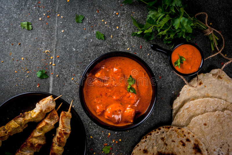Tikka masala, butter chicken curry. Indian food. Traditional dish spicy chicken tikka masala, butter chicken curry, with indian naan butter bread, spices, herbs stock photography