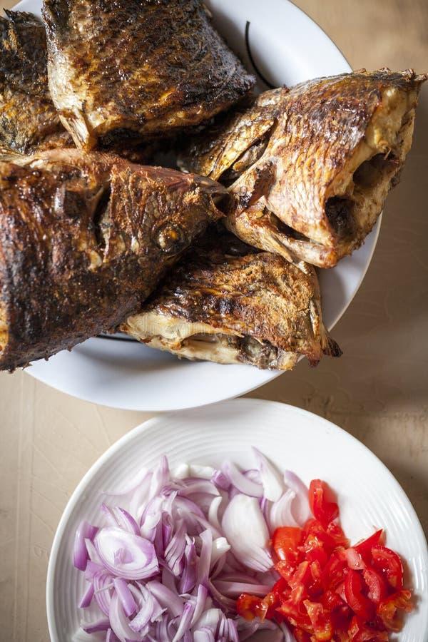 Tilapia al forno servito con la salsa di peperone immagini stock
