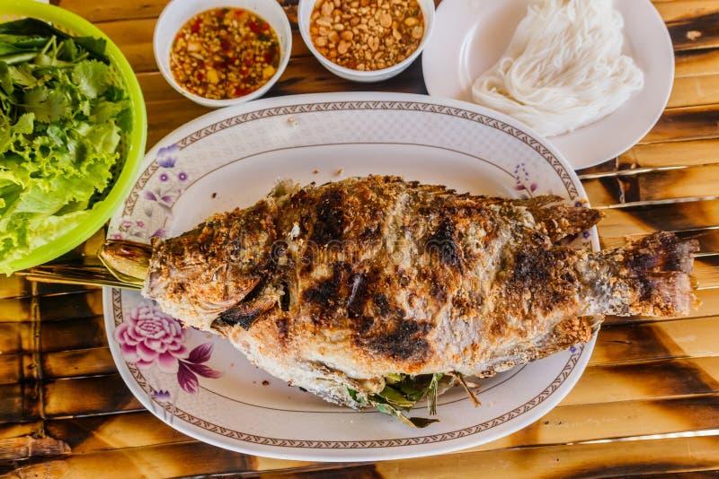 Tilapia arrostito sul piatto e sulla tavola di bambù immagini stock libere da diritti