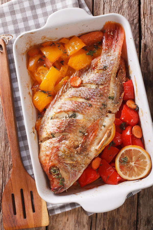 Tilapia baked with vegetables and thyme close up in baking dish. royalty free stock photos