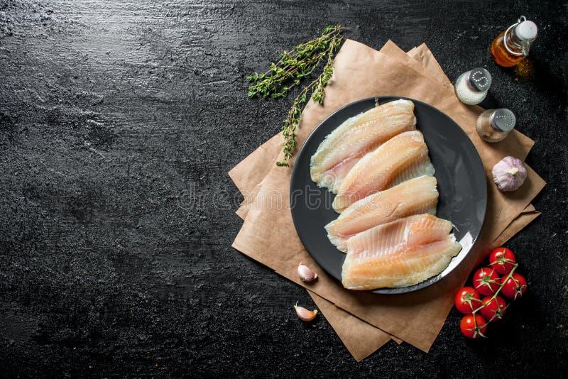 Tilapia Fischfilet auf einer Platte mit Papier, Gew?rzen, Thymian und Tomaten stockfotos