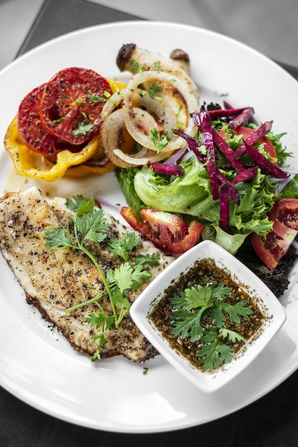 Tilapia fish fillet with mixed salad and grilled vegetables stock photo