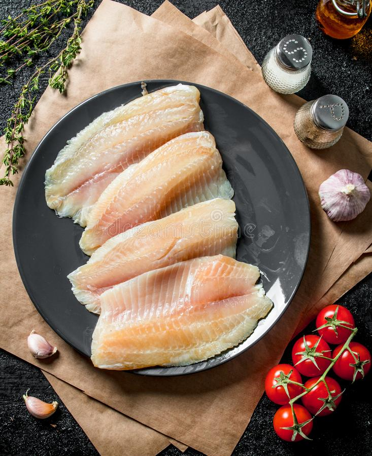 Tilapia fish fillet on a plate with paper, spices, thyme and tomatoes stock image